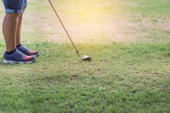 Golfer with metal golf club preparing to drive the golf ball on the fairway Royalty Free Stock Image