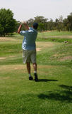 Golfer in motion. Hitting a ball Stock Images