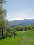 Golfer and Mount Etna. Golfer teeing off and view of the Etna volcano on background Royalty Free Stock Photo