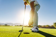 Golfer picking the ball from hole after put. Shot of a golf player taking out the ball from hole. Golfer picking the ball from hole after successful put Stock Images