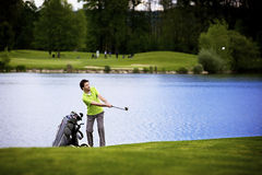 Golfer pitching at lake. Golf player pitching golf ball at lake with ball in the air Stock Images
