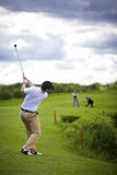 Golfer pitching over obstacle Stock Photography