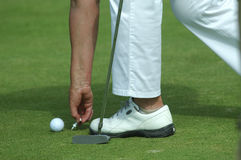 Golfer placing golf ball on a tee Stock Photo