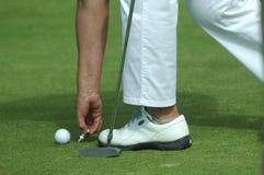 Golfer placing golf ball on a tee Stock Photo