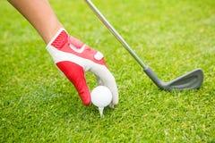 Golfer placing golf ball on tee Stock Photo