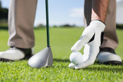 Golfer placing golf ball on tee Stock Photo