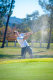 Golfer playing a chip shot onto the green Stock Photos