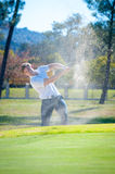 Golfer playing a chip shot onto the green Royalty Free Stock Photography