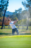 Golfer playing a chip shot onto the green Stock Photo