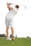 Golfer playing a game of golf. Rear view shot of a man playing a game of golf Stock Photo