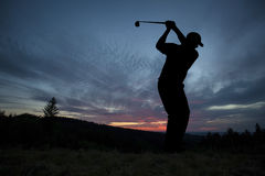Golfer playing golf during sunset at competition event Royalty Free Stock Photo