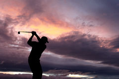 Golfer playing golf during sunset at competition event Royalty Free Stock Images