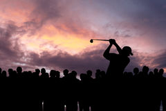 Golfer playing golf during sunset at competition event Royalty Free Stock Photos