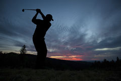 Golfer playing golf during sunset at competition event Stock Images