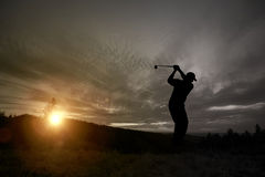 Golfer playing golf during sunset at competition event Stock Photo