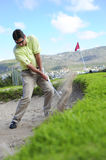 Golfer playing out of a sand trap. A professional golfer playing a shot out of a sand-trap with excellent control Stock Images
