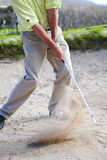 Golfer playing out of a sand trap. A professional golfer playing a shot out of a sand-trap with excellent control Royalty Free Stock Image