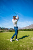 Golfer playing a shot on the fairway Stock Photos
