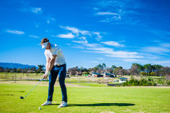 Golfer playing a shot on the fairway Stock Photography