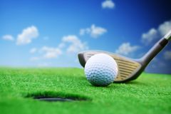 Golfer prepared for a golf shut in green grass in a sunny day with clear blue sky Royalty Free Stock Images