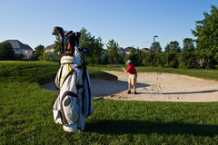 Golfer prepares to hit the golf ball from the sand trap Stock Photos