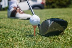 Golfer Hitting Golf Ball off Tee. Golfer preparing to hit a white golf ball off of a tee Royalty Free Stock Photos