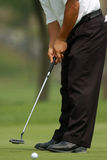 Golfer putting 01. Golfer putts ball into hole on the green Royalty Free Stock Photo