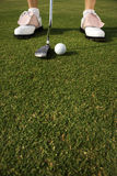 Golfer Putting. Closeup of a golf ball and the shoes of a golfer about to putt. Vertical shot Stock Photo