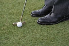 Golfer Putting. A man in black business shoes stands on a golf green, about to putt Stock Image