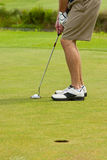 Golfer putting. Toward hole, focus on putter Royalty Free Stock Photo