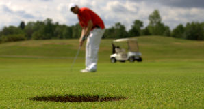 Golfer putting the ball. Hole on the  green of a golf course with golfer about to put the ball and a white electric caddy carl out of focus Stock Photos