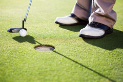 Golfer putting ball on the green Stock Photography