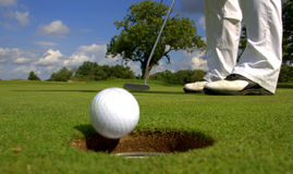Golfer putting ball into hole