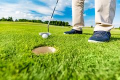 Golfer putting ball in the hole on a golf course. Golfer putting ball in the hole on a golf course close up. Focus on the ball Royalty Free Stock Image
