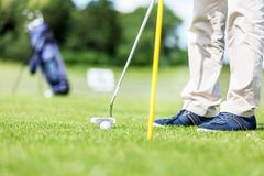 Golfer putting ball in the hole on a golf course. Golfer putting ball in the hole on a golf course close up. Focus on the ball Royalty Free Stock Photography