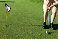 Golfer putting the golf ball Stock Photos
