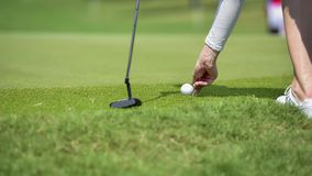 Golfer putting golf ball on green grass for check fairway to hole. On golf course Royalty Free Stock Photo