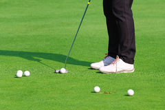 Golfer putting a golf ball in to hole Royalty Free Stock Photos