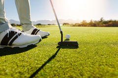 Golfer putting golf ball to hole. Male golfer on putting green about to take the shot. Golf player putting golf ball to hole Stock Image