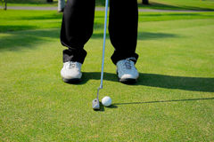 Golfer putting golf ball Stock Images