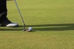 Golfer putting on the green. Putter touching the ball Royalty Free Stock Photo
