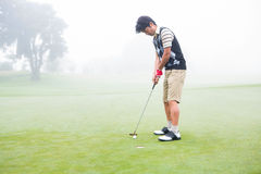 Golfer on the putting green at the hole Royalty Free Stock Photos
