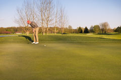 Golfer putting at green. Stock Photography