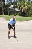 Golfer putting from a sand trap Royalty Free Stock Photography