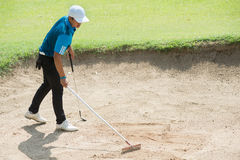 Golfer racking sand at golf course, thailand Stock Photos