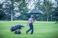Golfer on a Rainy Day Leaving the Golf Course. (the game is annulled because of the storm Royalty Free Stock Photos