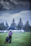Golfer on a Rainy Day Leaving the Golf Course. (the game is annulled because of the storm Royalty Free Stock Photo