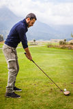 Golfer ready to hit. A golf player making a swing on a vibrant beautiful golf course Stock Photo