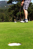 Golfer ready to putt. Golfer lines up putt with ball on green Stock Photo