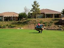 Golfer's Putting. A golfer lines up his putt (resubmit - color enhanced, MR included Stock Image